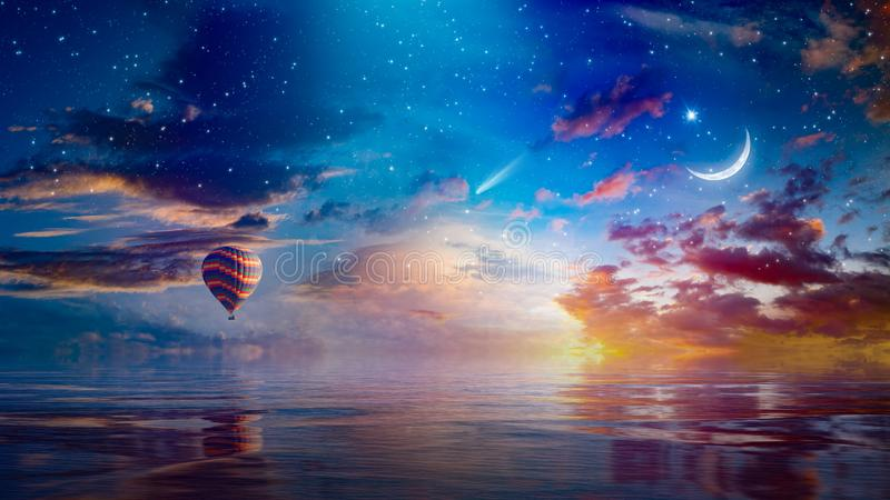 Crescent moon, hot air balloon and comet in sunset starry sky. Amazing surreal background - crescent moon and hot air balloon rising above serene sea in sunset royalty free stock images