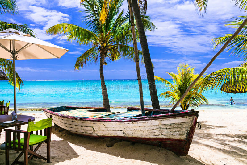amazing tropical holidays. Beach restaurant with old boat. Mauritius island royalty free stock image