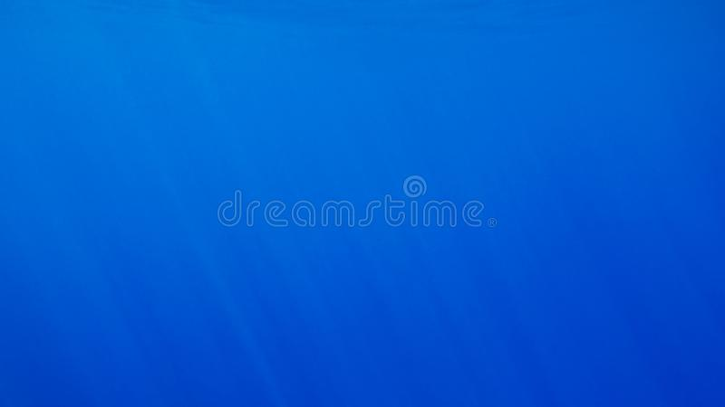 Amazing underwater image of sun and light rays shining through deep ocean water surface stock photo