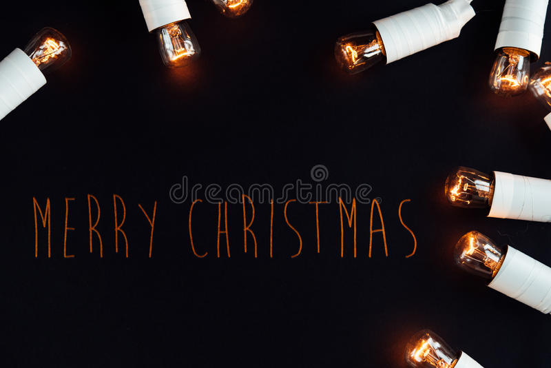 amazing unique christmas golden vintage garland lights on stylish black background, merry christmas text stock photos