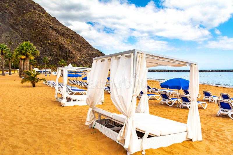 Amazing view of beach las Teresitas with yellow sand, umbrellas, longues and palm trees. Location: Santa Cruz de Tenerife,. Tenerife, Canary Islands. Artistic royalty free stock images