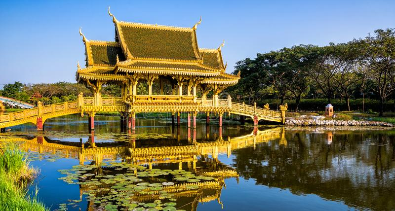 Amazing view of beautiful Golden Bridge and Pavilion of the Enlightened with reflection in the water. Location: Ancient City Park. Muang Boran, Samut Prakan royalty free stock photo