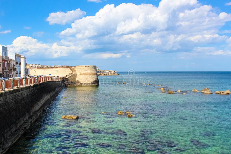 Amazing view of blue sea and adjacent city coast in Syracuse, Sicily, Italy on a sunny day with blue sky. Stones in sea water. Photographed in Ortygia Island stock image