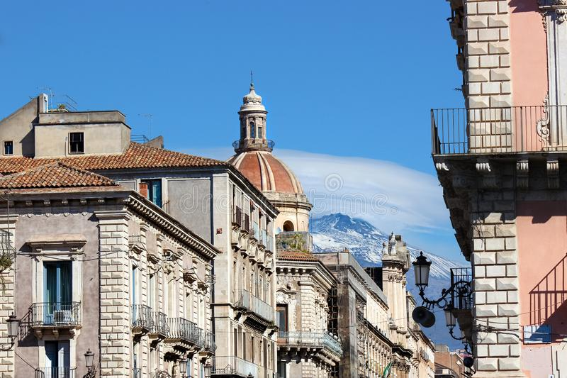 Amazing view of Catania Cathedral of Saint Agatha with adjacent buildings and Etna volcano in the background. Mount Etna. Is located nearby the Sicilian city stock images