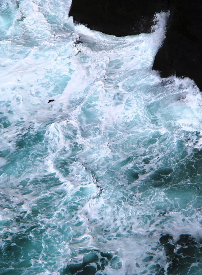 Magnificent colors of water while powerful waves crashing into rocks stock image