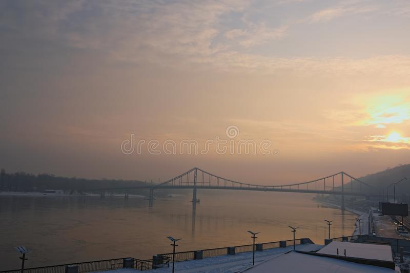 Amazing view on the Dnipro River and Footbridge. Winter sunrise on foggy morning. Kyiv, Ukraine stock image
