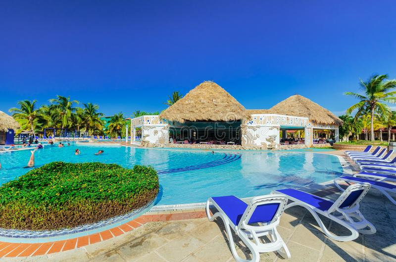 Amazing view of hotel grounds with nice inviting swimming pool and people relaxing in water in tropical garden royalty free stock photo