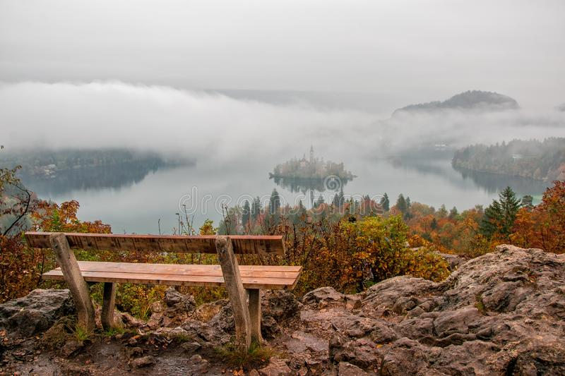 Amazing view of Lake Bled at foggy autumn morning wiyh wooden bench on foreground stock photography