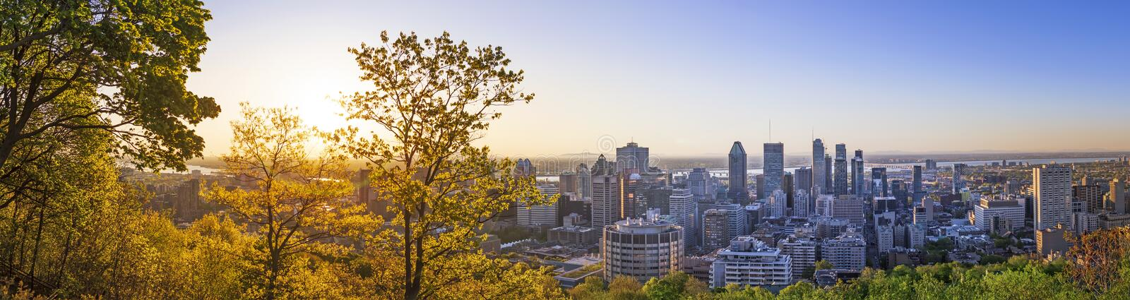 Amazing view of Montreal city at sunrise with colorful blue architecture, green and yellow landscape. Beautiful sky and sun light royalty free stock photos