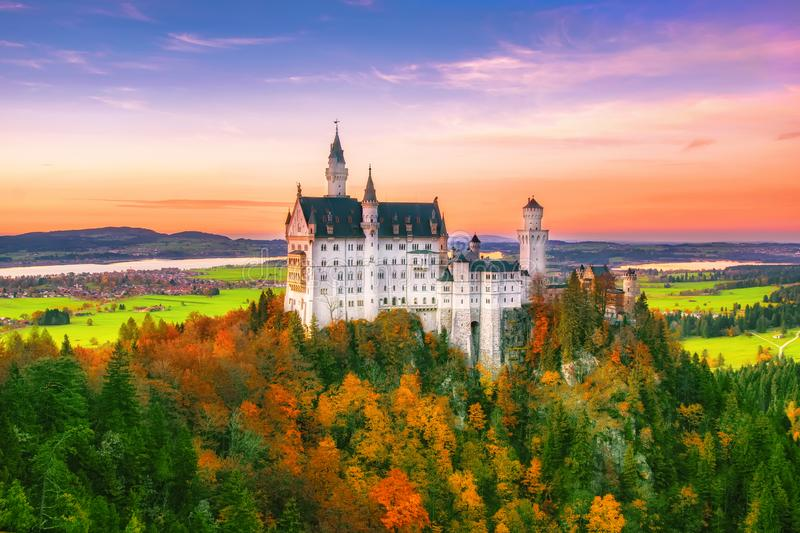 Amazing view on Neuschwanstein Castle at autumn evening, Bavaria, Germany. Amazing view on Neuschwanstein Castle with picturesque sky and colorful trees at stock image