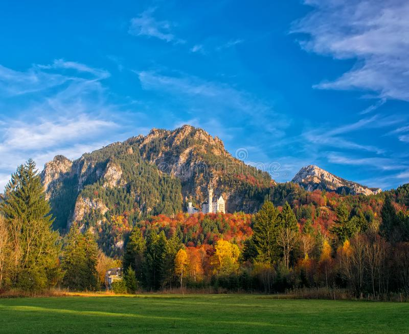Amazing view on Neuschwanstein Castle with picturesque sky and colorful trees at autumn sunny day, Bavaria, Germany. royalty free stock photos