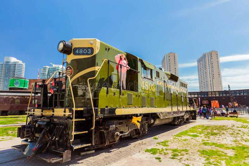 Amazing view of old style retro diesel train with little girl looking up in down town district area on sunny weekend day royalty free stock photos