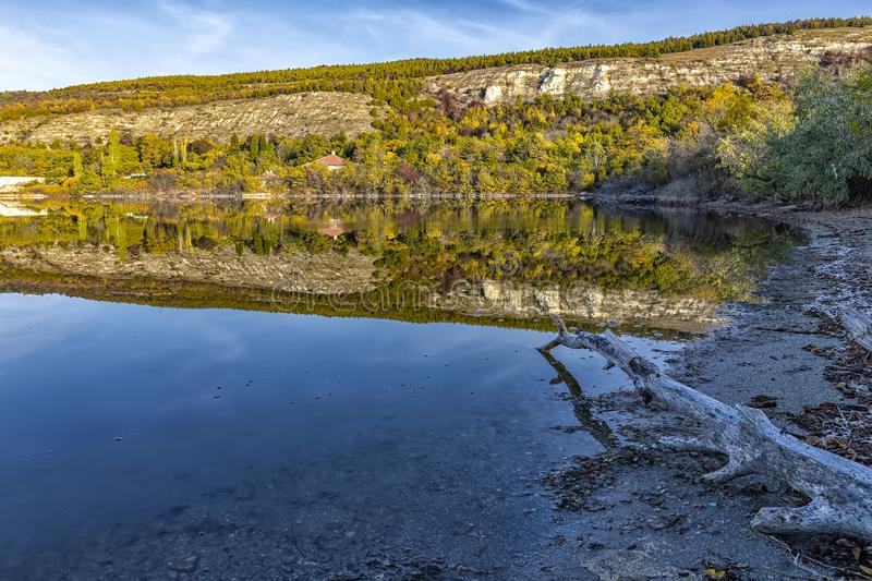 An old tree and mountain hills with autumn colors reflected in still lake water. Amazing view from the shore of an old tree and mountain hills with autumn colors royalty free stock images