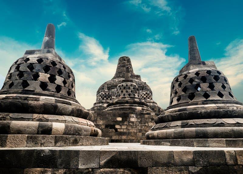 Borobudur Buddhist temple. Magelang, Java, Indonesia. Amazing view of stone stupas at ancient Borobudur Buddhist temple against beautiful landscape on background royalty free stock photos