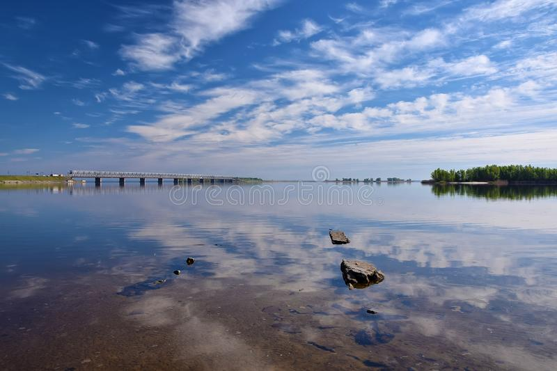 Amazing view to bridge and dam across the Dnieper river, Cherkasy, Ukraine at sunny day. Beautiful clouds reflected in surface water at sunny summer day. Bridge royalty free stock images