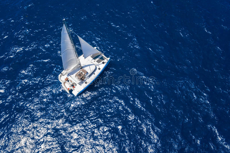 Amazing view to Catamaran cruising in open sea at windy day. Drone view - birds eye angle.  stock photo