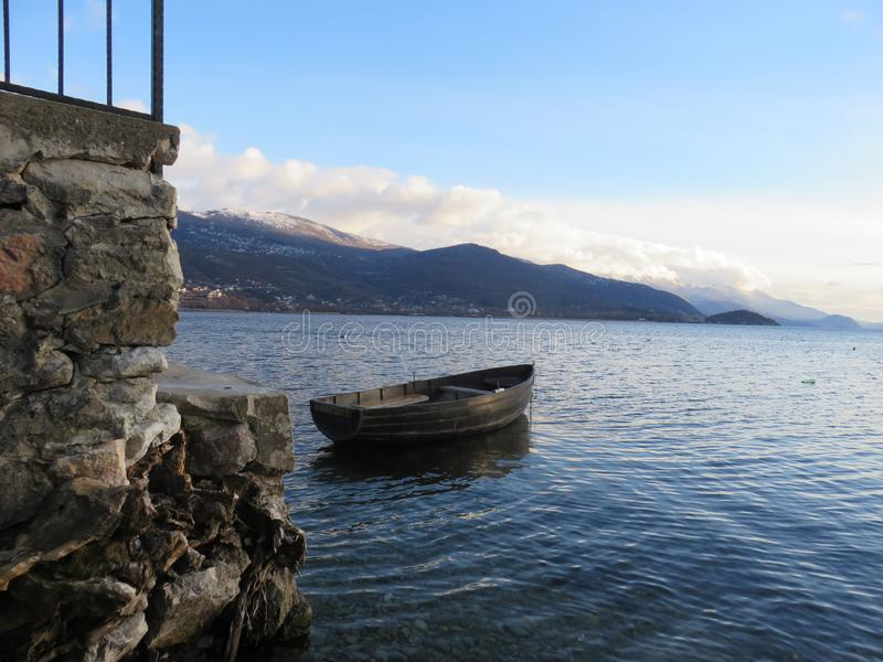 Amazing view to Ohrid lake, Macedonia, boat, moutain, sky. Photo of amazing view to Ohrid lake, Macedonia, fishing boat floating, one part of mountain and light royalty free stock photo