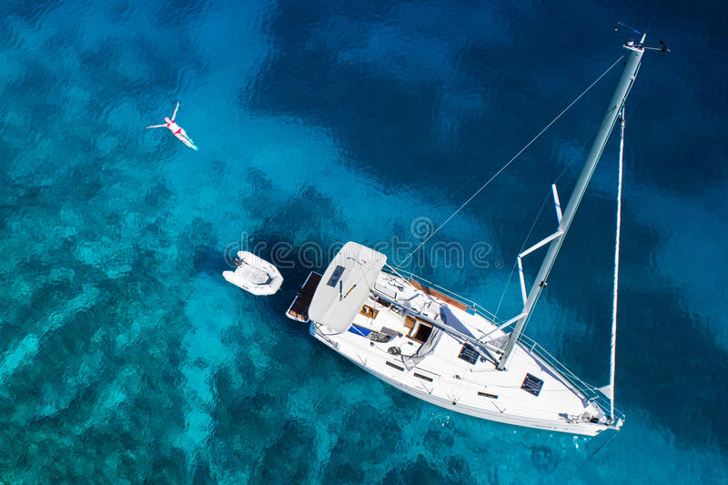 Amazing view to yacht, swimming woman and clear water in caribbean paradise royalty free stock photography