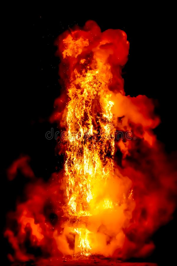amazing violent explosion of fire in the dark night. The combustion creates big flames, gas en generates a wide light. Vertical royalty free stock image