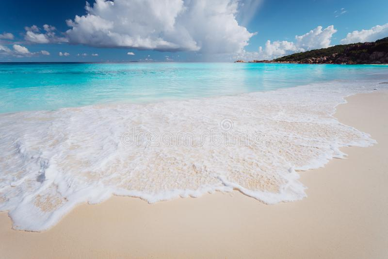 Amazing water colors of Grande Anse, La Digue Island Seychelles. Sea foam on Tropical beach with impressive white clouds stock photo