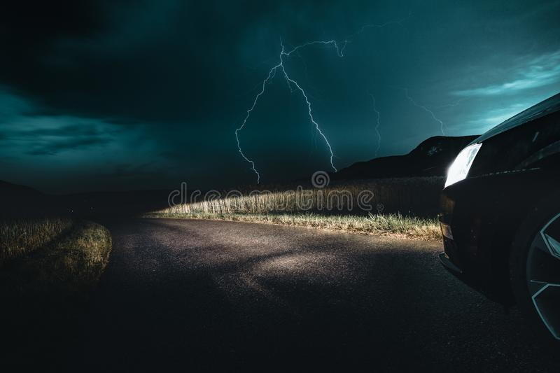 Amazing Weather Storm Photo with Big Bright Lightning Bolt Strike Coming from Dark Moody Sky. Black car is standing in the front of a field in austria stock photo