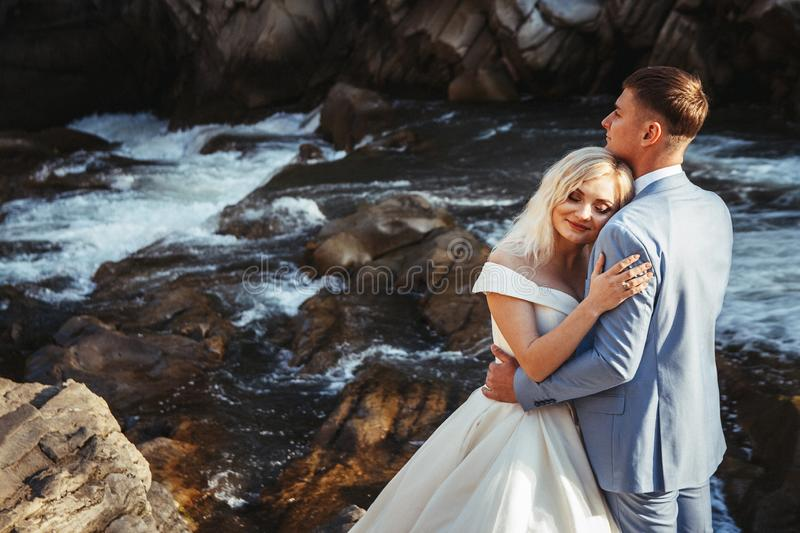 Amazing wedding couple, bride and groom holding hands on a mountains and rivers background. Cute girl in white dress stock image