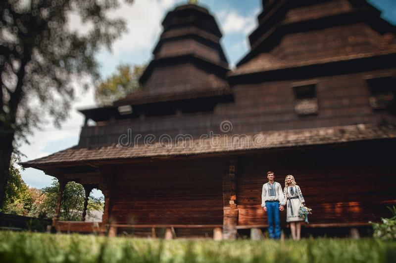Amazing wedding couple in an embroidereds shirt with a bunch of flowers on the background of a wooden house royalty free stock photos