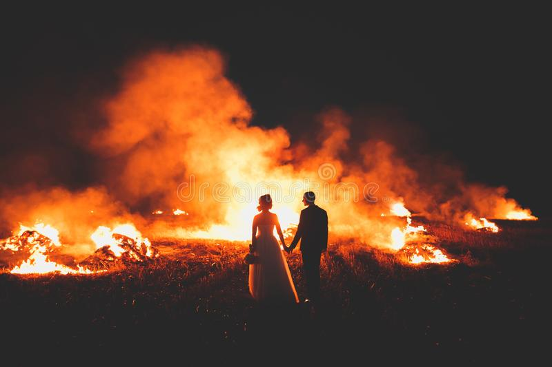 Amazing wedding couple near the fire at night.  royalty free stock image