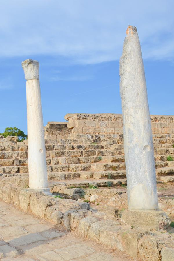 Amazing white Corinthian columns captured on a vertical photography with ancient ruins in the background and blue sky above royalty free stock photo