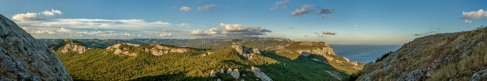 Amazing wide panoramic mountain view with the nice sky and the sea in the warm sun light in afternoon stock photos