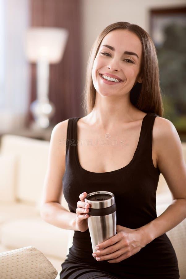 Amazing woman holding a thermo mug. Feeling happy. Amazing confident beautiful business woman holding a thermo mug while sitting and looking at the camera royalty free stock image