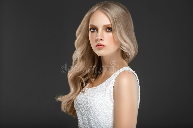 Amazing woman portrait. Beautiful girl with long wavy hair. Blonde model with hairstyle over black background stock image