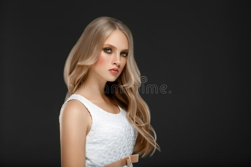 Amazing woman portrait. Beautiful girl with long wavy hair. Blonde model with hairstyle over black background royalty free stock images