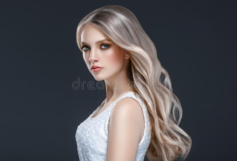 Amazing woman portrait. Beautiful girl with long wavy hair. Blonde model with hairstyle over black background royalty free stock image