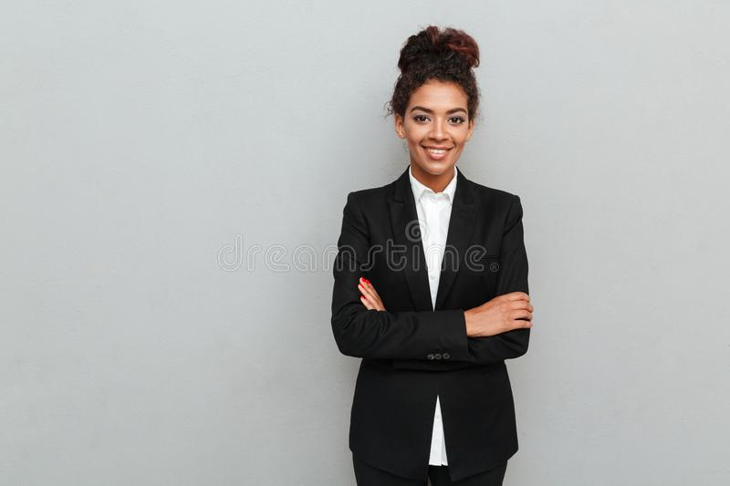 Amazing young african business woman standing over grey wall royalty free stock photography