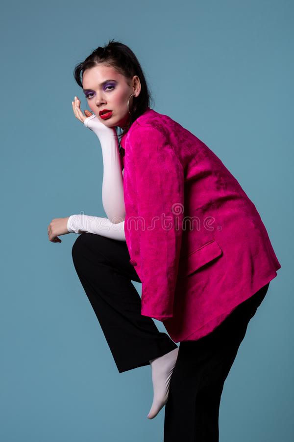 Amazing young brunett woman in trendy pink jacket standing on one leg stock images