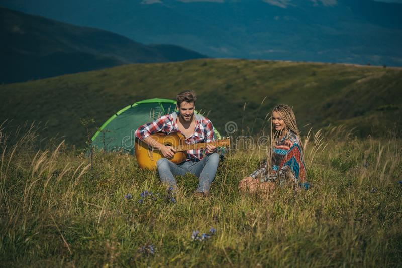 Amazing young loving couple on camp outside in free alternative vacation camping over mountains. Happy travelers getting royalty free stock photography