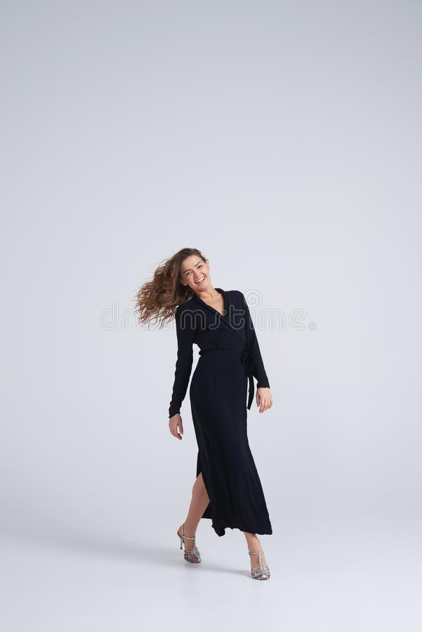 Amazing young stylish woman in black dress posing at camera royalty free stock images
