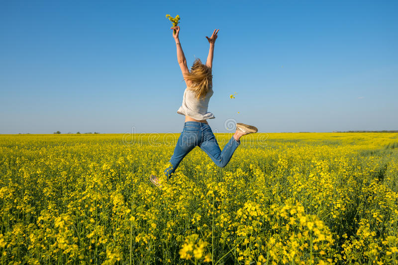Amazing young woman, blonde jumping and having fun in a field royalty free stock images