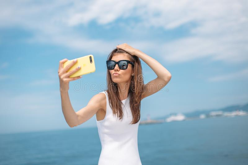 Young brunette girl making selfie using phone posing on luxury yacht. Amazing young woman with brown hair wearing white dress making selfie with cell phone on stock photo