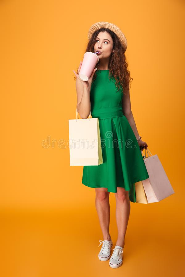 Amazing young woman drinking aerated water holding shopping bags. Photo of amazing young woman standing isolated over yellow background. Looking aside drinking royalty free stock photography