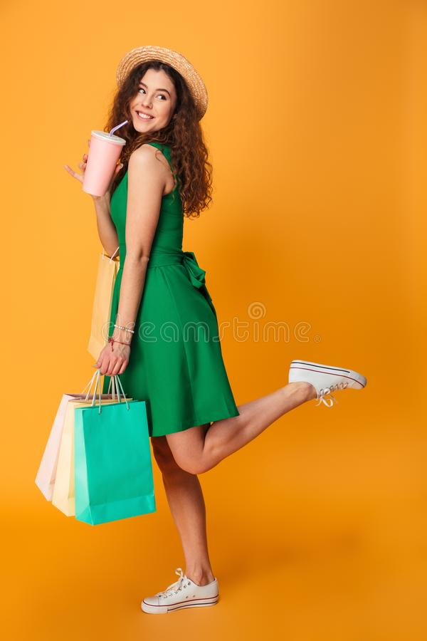 Amazing young woman drinking aerated water holding shopping bags. Photo of amazing young woman standing isolated over yellow background. Looking aside drinking royalty free stock photo