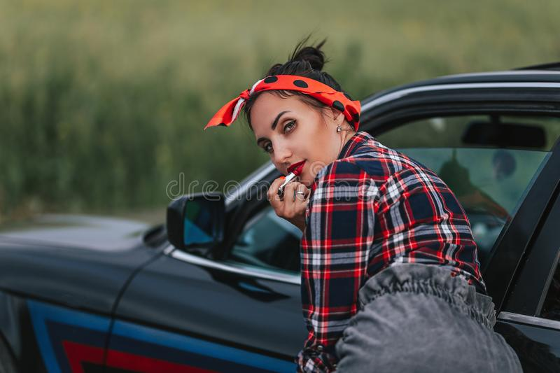 Amazing young woman,outdoor portrait,fashionable model drive car at her casual sexy outfit,amazing hairstyle,make-up,hight royalty free stock image