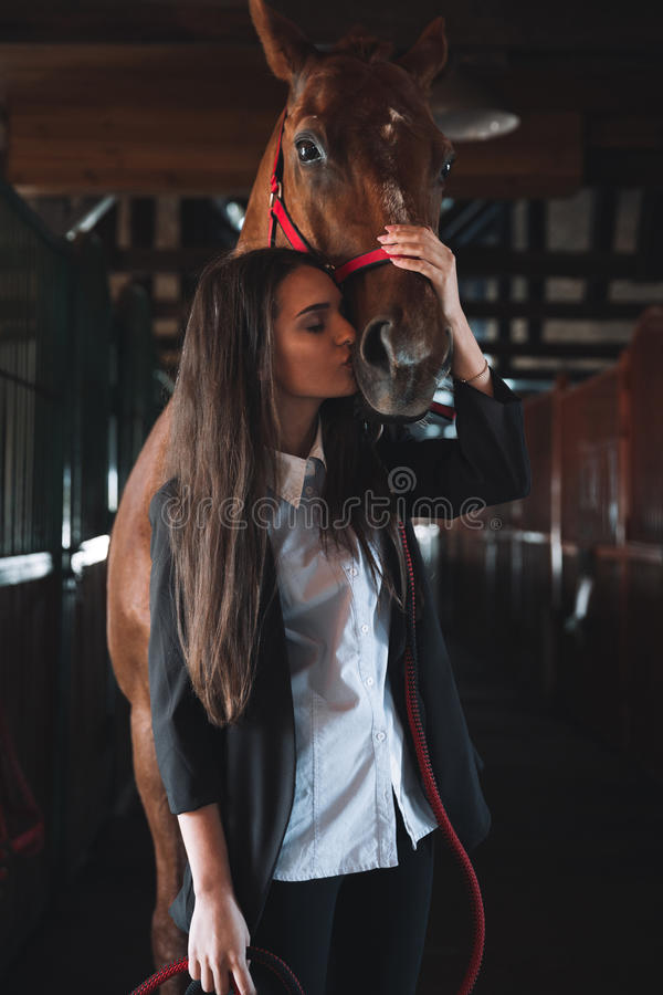 Amazing young woman standing in barn kissing her horse stock photo