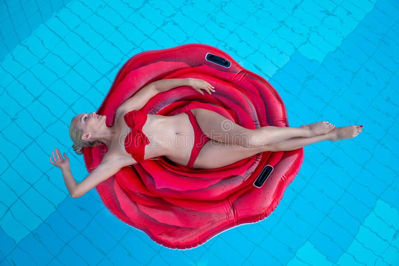Amazingly beautiful girl in a red bikini on an air mattress a red rose swims in the pool of a beautiful hotel, summer vacation, stock image