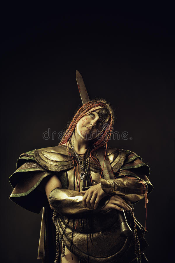 Amazon in contemplation. Bloody amazon with sword in contemplation over dark background stock image