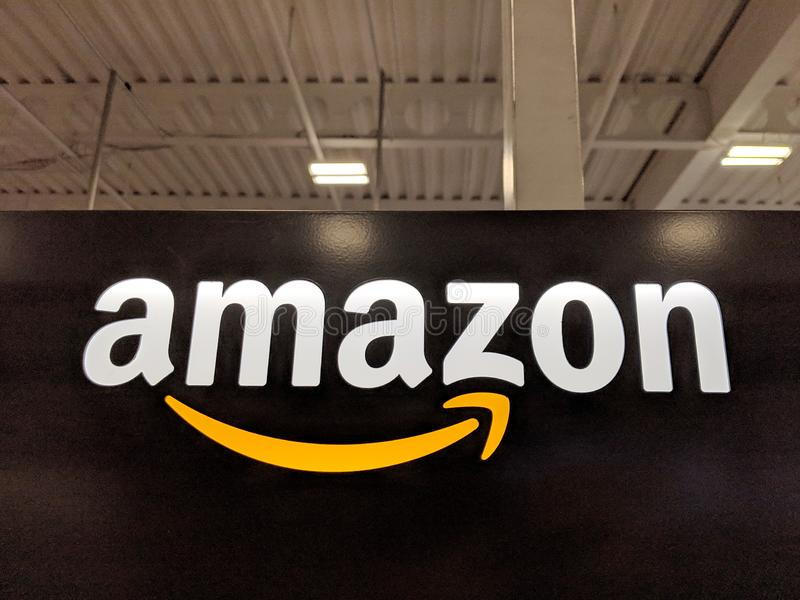 Amazon logo on black shiny wall in Honolulu Best Buy store. Honolulu -  March 16, 2019:  Amazon logo on black shiny wall in Honolulu Best Buy store.  Amazon is royalty free stock photo