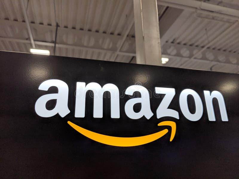 Amazon logo on black shiny wall in Honolulu Best Buy store. Honolulu -  March 16, 2019:  Amazon logo on black shiny wall in Honolulu Best Buy store.  Amazon is stock photos