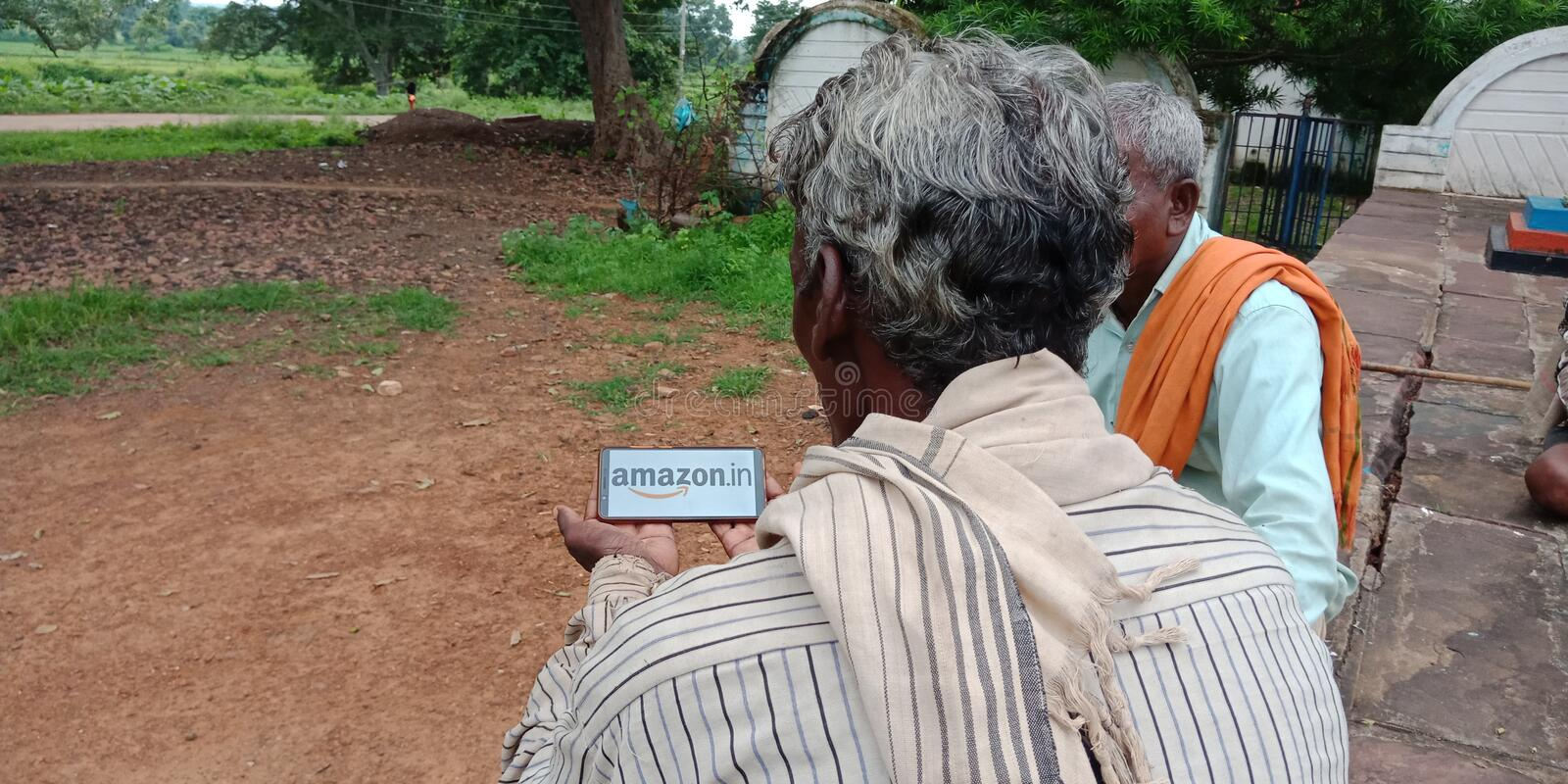 Amazon logo displayed on mobile phone screen online at indian village area stock photos