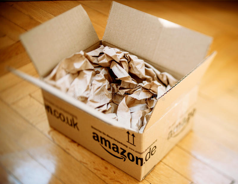 Amazon parcel opened on home parquet floor stock photos